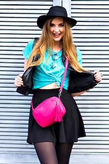 トレンディな流行に敏感な金髪女性、幸せな肯定的な感情、ステア、明るいスタイリッシュな外観、サングラス、帽子、革のジャケット、ボディバッグ全体でポーズの屋外グランジファッションポートレート。