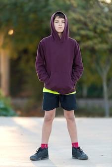公園の自然の背景の上のフードの屋外ハンサムな男の子の肖像画の十代の少年