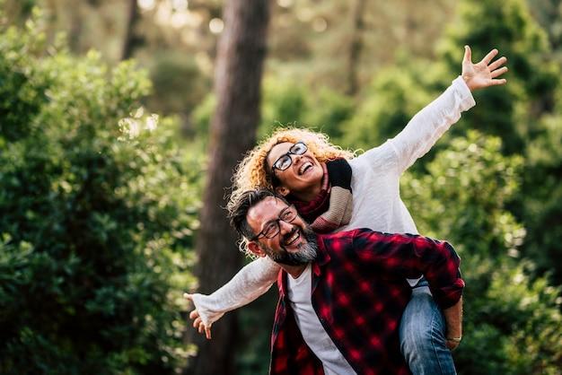 眼鏡をかけた屋外の幸せで陽気な白人カップルは楽しんで、自然とレジャー活動を一緒に楽しんでいます-男性は女性を運び、両方ともたくさん笑います