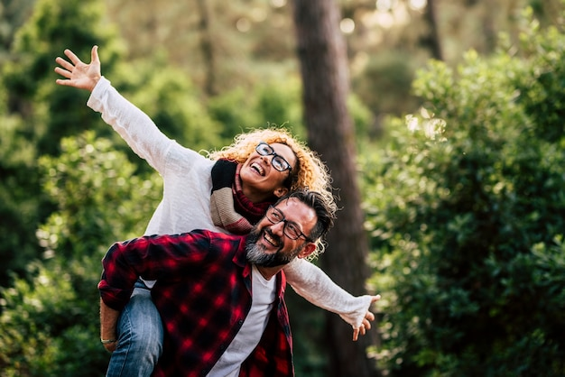 眼鏡をかけた屋外の幸せで陽気な白人カップルは、自然とレジャー活動を一緒に楽しんで楽しんでいます