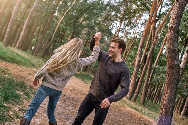 Outdoor happy couple in love posing in autumn forest. young woman and man are dancing outdoor
