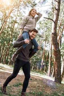 Outdoor happy couple in love posing in autumn forest. young woman and man having fun outdoor
