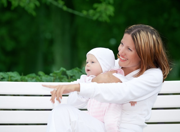 赤ちゃんと一緒に屋外の幸せな母親(顔に焦点を当てる)