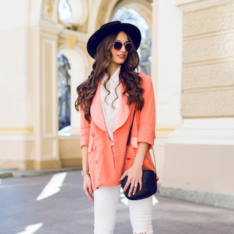 Outdoor hight fashion portrait of stylish casual woman in black hat, pink suit, white blouse posing on old street