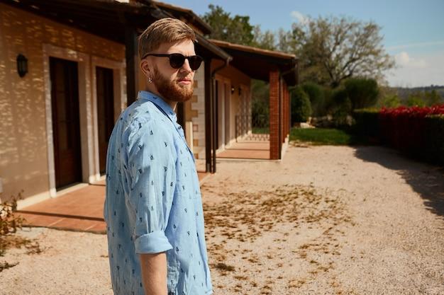 Immagine orizzontale all'aperto di attraente giovane ragazzo europeo con barba sfocata in posa