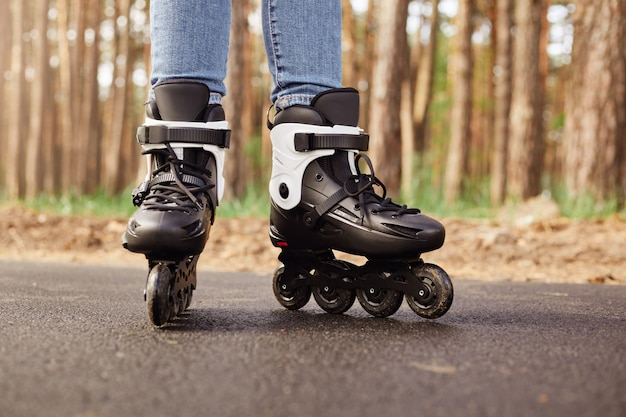 Outdoor horizontal picture of black and white roller skates being on road over tree wall in forest, having ride, sticking to active lifestyle, rollerblading in spring. people and hobby concept.
