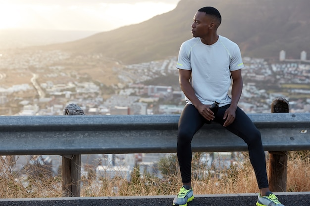 Outdoor horizontal shot of dark skinned man in casual t shirt, sneakers, carries bottle of water, focused aside, has break after morning workout alone, feels dehydrated, has morning exercises
