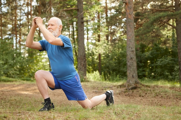 Outdoor image of active senior man in running shoes stepping forward doing lunges, keeping hands together in front of his face. attractive healthy male pensioner stretching leg muscles in forest