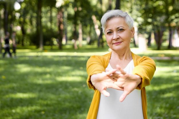 Immagine esterna di attraente donna in pensione dai capelli grigi che allunga i muscoli delle braccia, riscaldando il corpo prima della corsa mattutina nel parco. concetto di persone, sport, salute, fitness, invecchiamento, ricreazione e attività