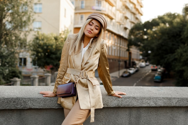 Outdoor image of elegant european woman walking in autumn city . beige cap and jacket. stylish accessories.