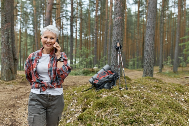 Immagine esterna di energica donna in pensione in abbigliamento sportivo che cammina nella foresta, avendo conversazione telefonica, sorridente, zaino e materassino sotto l'albero sullo sfondo. persone, viaggi e tecnologia