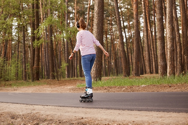Outdoor image of energetic sleder young woman having training, being active, rollerblading alone, having rest, relaxing, enjoying weekends, being on road, listening to music. lifestyle concept.