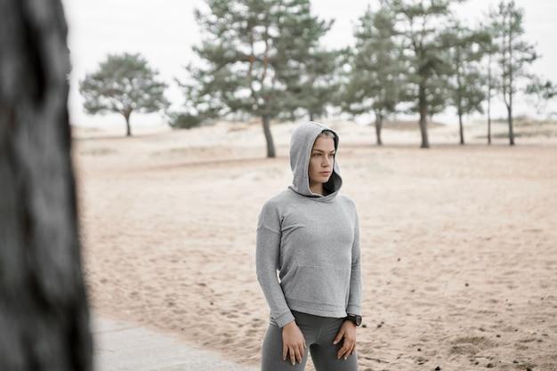 Immagine all'aperto di giovane donna snella in forma vestita in abiti sportivi alla moda in posa all'esterno con spiaggia sabbiosa e alberi di pino sullo sfondo, esercitando, facendo routine di allenamento mattutino. messa a fuoco selettiva