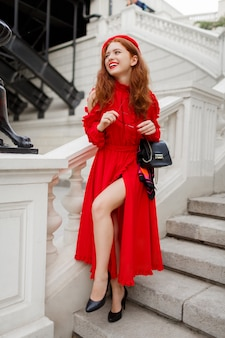 Outdoor image of gorgeous ginger woman in red beret and dress standing on stairs near bridge in beautiful european city.