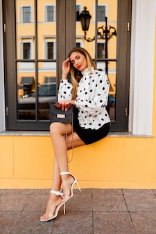 Outdoor image of gorgeous woman with legs in stylish spring clothes with small bag posing on the street on yellow.