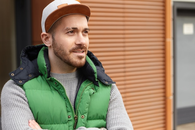 Outdoor image of handsome fashionable young caucasian man with trimmed beard and pierced eyebrow posing on street keeping arms folded, wearing cap and green nylon vest, opening mouth slightly