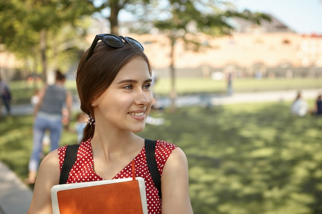 Outdoor image of happy pretty schoolgirl posing while having walk in park after lectures at college, smiling broadly, embracing copybooks