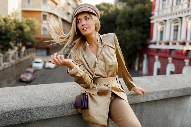 秋の街を歩くエレガントなヨーロッパの女性の屋外イメージ。ベージュのキャップとジャケット。スタイリッシュなアクセサリー。ファッショナブルな外観。