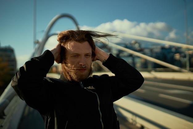 強風で耳を手で覆い、モダンな橋の上でポーズをとる、太いひげと長い髪の魅力的な若い男性ヒップスターの屋外画像。街並みを歩く鼻ピアスのスタイリッシュな男