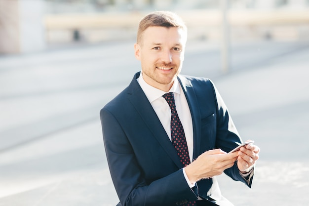 Outdoor image of successful male entrepereneur, wears formal black suit