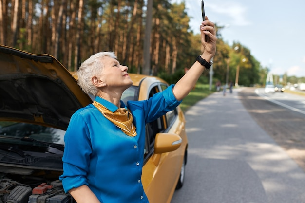 Outdoor image of unhappy middle aged woman standing on road by broken car with open hood raising hand with mobile phone, looking for network signal, trying to call for assistance.