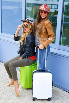 Outdoor lifestyle bright portrait of two best friends girls walking with their luggage near airport, wearing comfy bright stylish clothes, ready for travel and new emotions