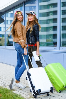 Outdoor lifestyle bright portrait of two best friends girls walking with their luggage near airport