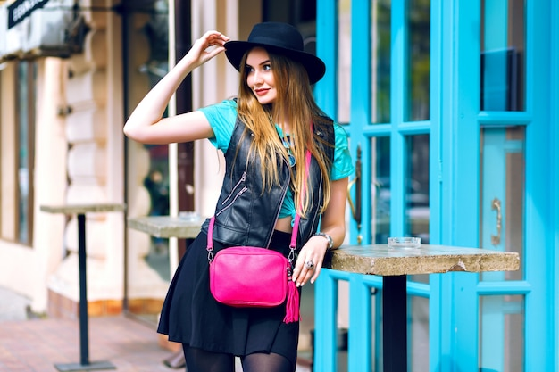 Outdoor lifestyle fashion portrait of pretty blonde woman walking and enjoy summer sunny day,stylish outfit, mini skirt, vintage hat, biker jacket, bright details and accessorizes, europa city center