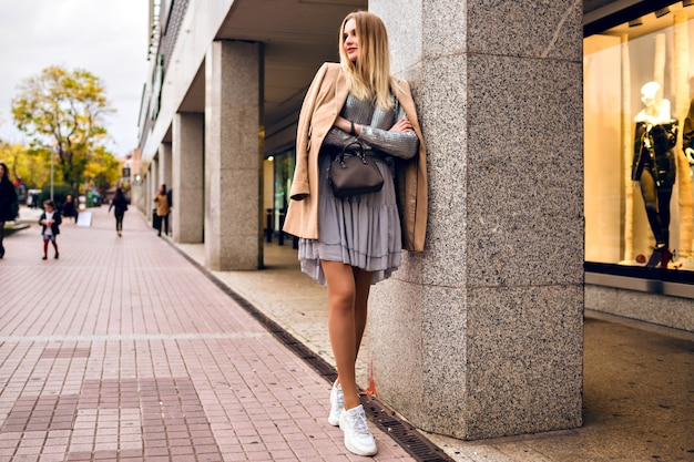 Outdoor lifestyle fashion portrait of pretty elegant glamour blonde woman with long legs, wearing trendy sneakers, dress sweater and coat, posing at europe city, traveling alone.