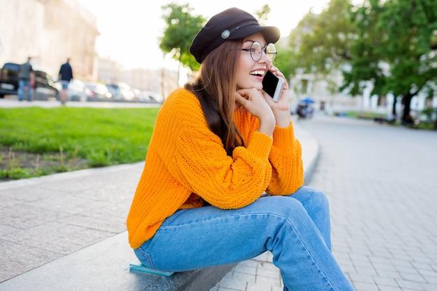 Внешний образ жизни романтической мечтательной женщины, сидя на тротуаре и разговаривая по мобильному телефону.