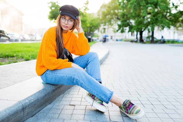 Outdoor lifestyle image of romantic   dreamy woman sitting on sidewalk and enjoying  evening