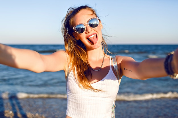 Outdoor lifestyle portrait of funny happy girl traveling to the ocean alone, making selfie at the beach, happy positive emotions, mirrored sunglasses, white crop top and backpack, joy, motion.