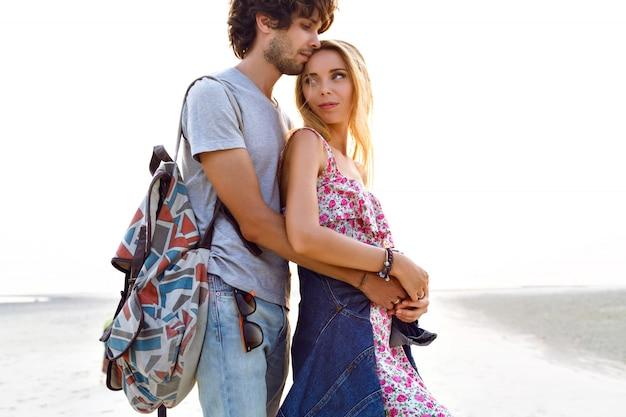해변에서 포즈를 취하는 사랑에 놀라운 꽤 젊은 부부의 야외 라이프 스타일 초상화. 세련된 남녀가 포옹하고 함께 즐거운 시간을 보냅니다. 플로럴 드레스 백팩과 데님.