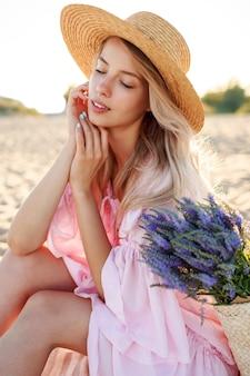 바다 근처 햇볕이 잘 드는 해변에 앉아 우아한 백인 여자의 야외 라이프 스타일 초상화. 밀짚 모자를 쓰고. 자연 배경.