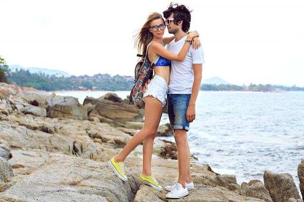 愛のポーズとかわいい石のビーチ、柔らかいトーンの色で楽しんで若い美しいカップルのアウトドアライフスタイルの肖像画。