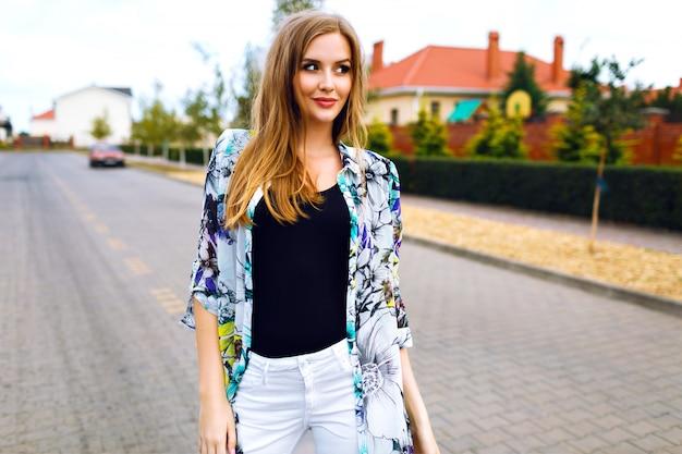 Ritratto di stile di vita all'aperto di donna abbastanza bionda, pantaloni bianchi, camicia floreale alla moda, trucco naturale per capelli lunghi, posa in campagna, stile di strada.