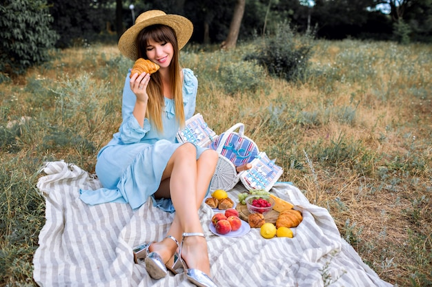 Outdoor lifestyle portrait of pretty elegant magnificent stylish woman wearing blue vintage feminine dress and straw hat
