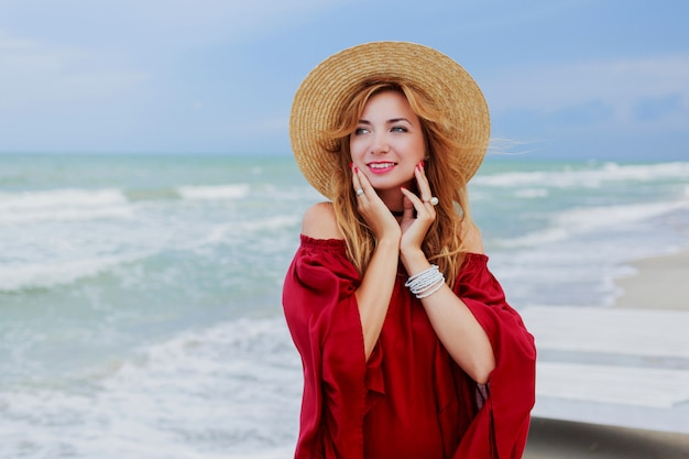Outdoor lifestyle portrait of pretty white ginger woman in stylish dress posing on the beach near ocean. blu sky. windy weather.