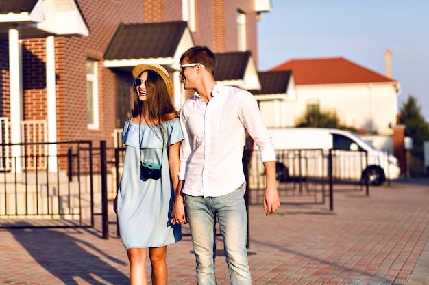 Outdoor lifestyle portrait of pretty young couple on romantic date having fun together, hugs and kisses, posing on the street, travel together, family portrait.