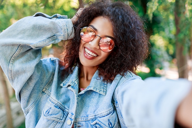 Outdoor lifestyle portrait of smiling  black woman in pink glasses