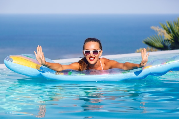 Outdoor lifestyle portrait of stunning young woman having fun at infinity pool with amazing view on tropical island, wearing bright bikini and sunglasses, swimming on air mattress.