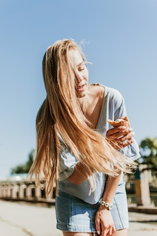 Outdoor lifestyle portrait of young trendy girl eating ice cream