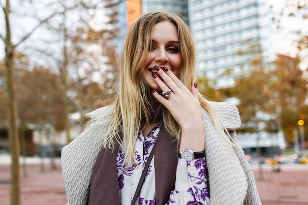 Открытый образ жизни положительный портрет красивой блондинки, улыбающейся в конце, наслаждается временем, гламурным элегантным нарядом, ношением платья и пальто, теплыми цветами, весенне-осенним временем.