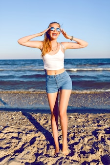 Ritratto di viaggio stile di vita all'aperto di giovane donna bionda in posa vicino all'oceano, top corto, shorty vintage mini denim hipster, zaino e occhiali da sole, pronto per avventure, corpo abbronzato sexy, gambe lunghe.