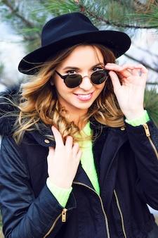 Ritratto di inverno di stile di vita all'aperto di ragazza sorridente abbastanza giocosa in posa vicino a abete rosso indossando occhiali da sole vintage retrò cappello e parka alla moda.