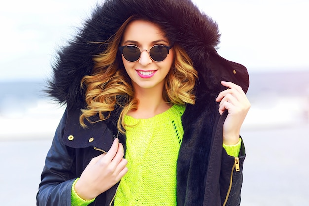 Lo stile di vita all'aperto appassisce il ritratto di giovane donna alla moda che indossa neon swather e giacca parka nera casual. look da strada.
