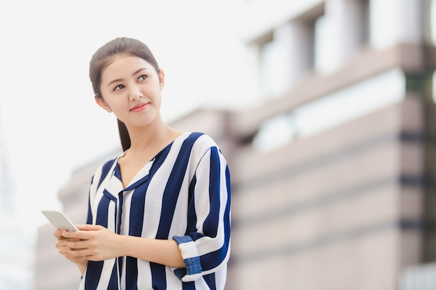 Outdoor lifestyle young businesswoman looking on smartphone
