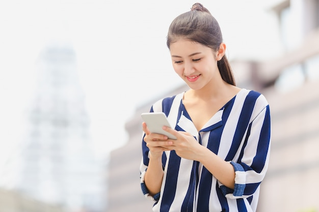 Outdoor lifestyle young woman looking on smartphone