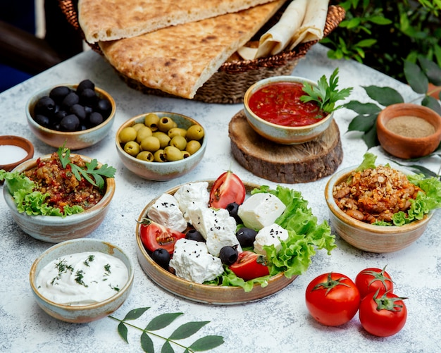 Outdoor lunch with salads, olives and bread