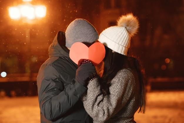通りで紙の心を持つ若いカップルの屋外の夜の肖像画